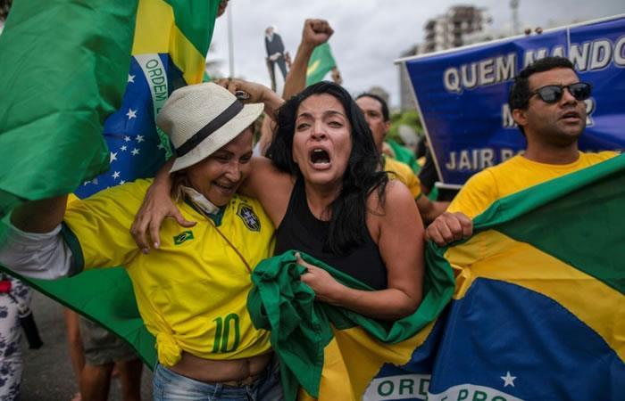 Simpatizantes de Jair Bolsonaro celebran tras los resultados de la primera vuelta electoral, frente a su residencia, en Barra da Tijuca, Rio de Janeiro. Foto: AFP.
