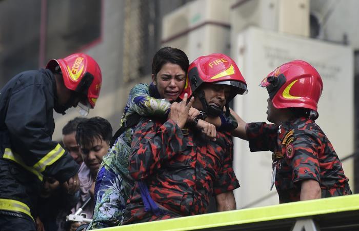 Un sobreviviente de Bangladesh reacciona después de ser rescatado por bomberos. Foto: AFP