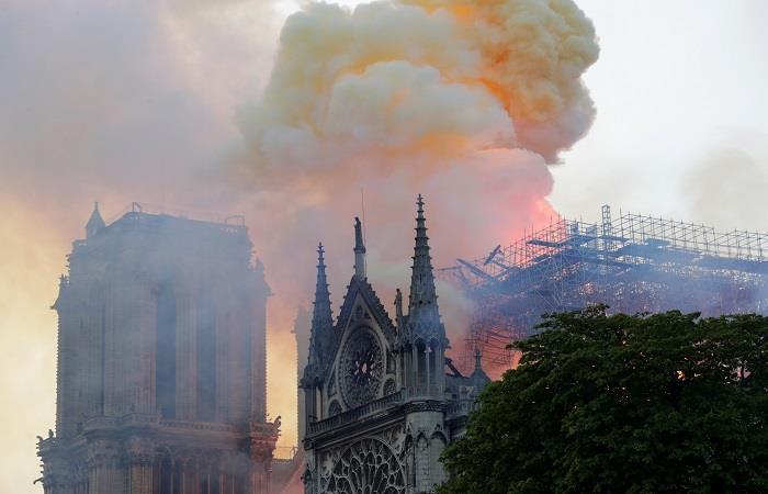 El edificio ya perdió su emblemática aguja, gracias al incendio que azota la construcción. Foto: AFP