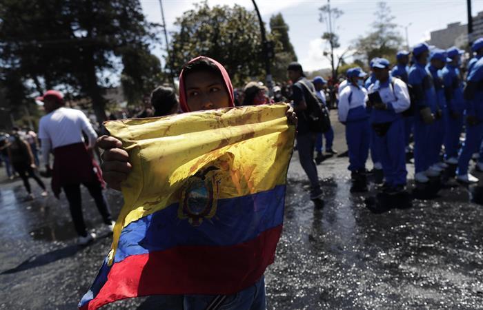 Un manifestante indígena sostiene una bandera ecuatoriana. Foto: EFE