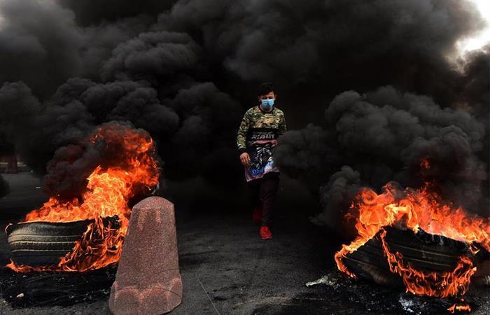 Manifestante iraquí pasa entre dos barricadas durante una protesta antigubernamental en Bagdad (Irak). Foto: EFE