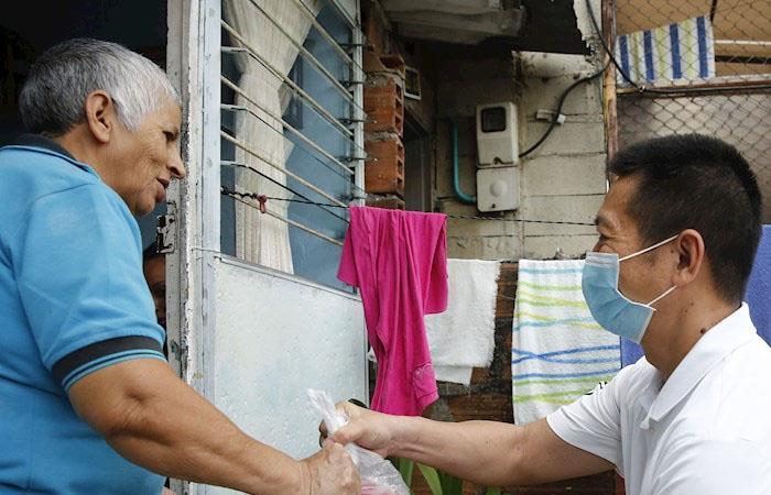 Los ciudadanos asiáticos fueron casa por casa entregando las ayudas. Foto: EFE