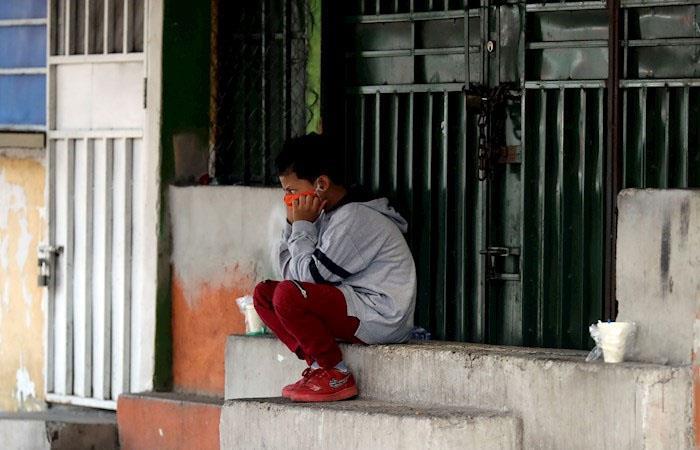 Un niño con tapabocas descansa en una acera de Tegucigalpa, Honduras. (). Foto: EFE