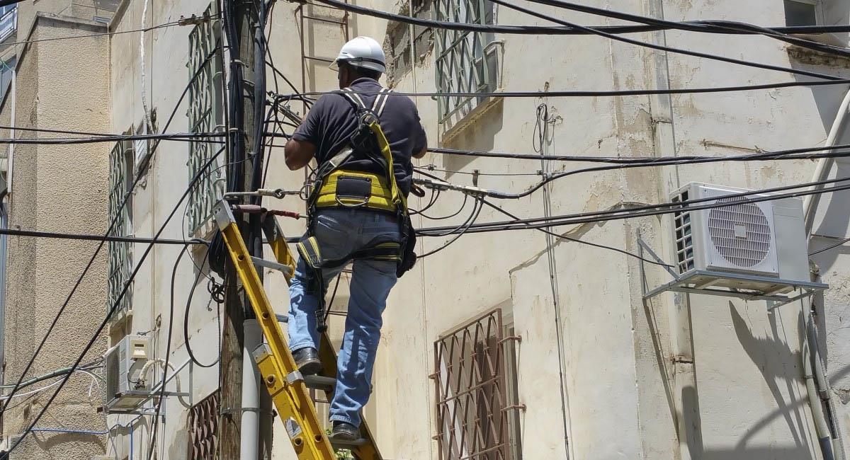 Empleado instala servicio de energía eléctrica en Colombia. Foto: Pxhere