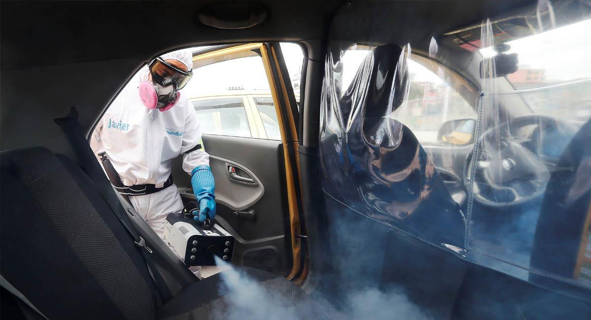 Un trabajador desinfecta el interior de un taxi en Bogotá. Foto: EFE