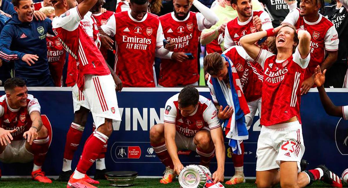 Los jugadores se ríen por romper el trofeo. Foto: EFE