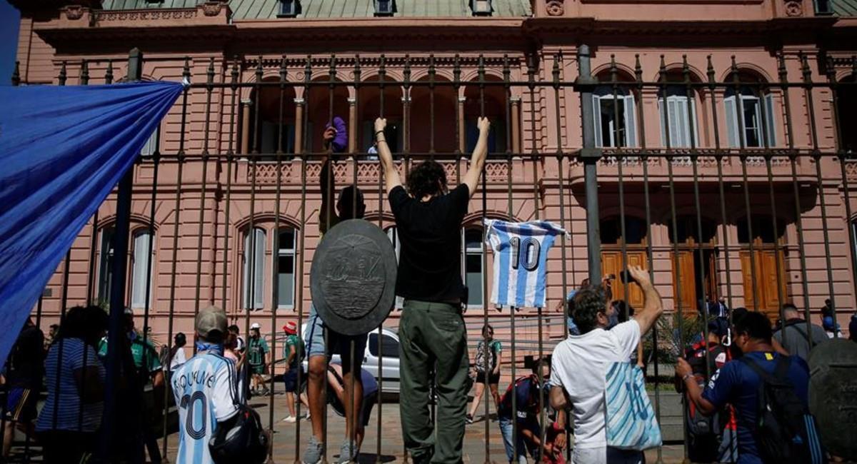 Seguidores de Maradona trepan la reja para poder ver el féretro de su ídolo. Foto: EFE