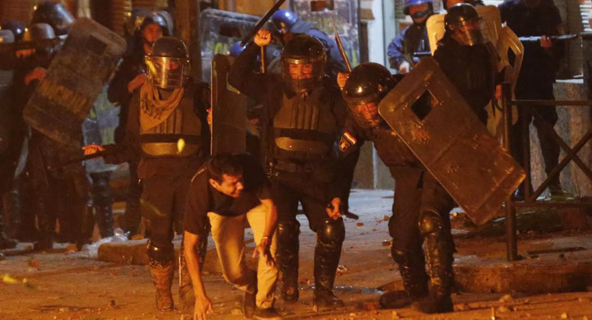 Policías golpean a un hombre en la ciudad de Asunción en medio de protestas por mal manejo gubernamental a la pandemia. Foto: Twitter @latablablog