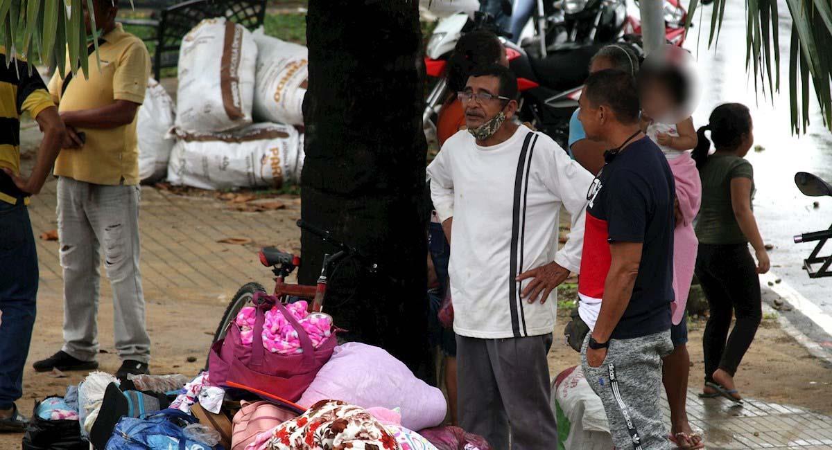 Migrantes esperan con sus pertenencias tras cruzar en botes desde La Victoria, en Venezuela. Foto: EFE