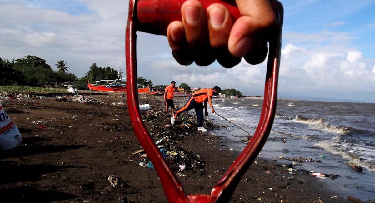 Personal de la Guardia Costera de Filipinas recogen basura a lo largo de la costa en la ciudad de Tanza. Foto: EFE