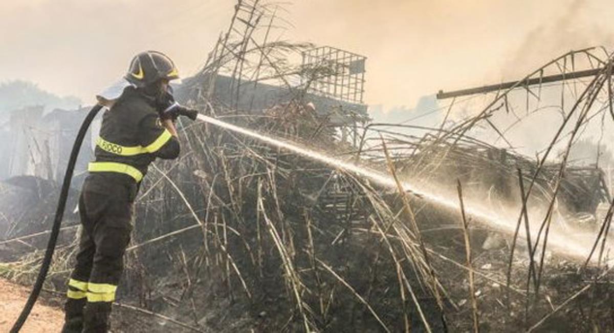Un bombero apaga las llamas en Sicilia, sur de Italia, en donde el fuego ha llegado a zonas urbanas. Foto: Twitter @ErnestoSuidry